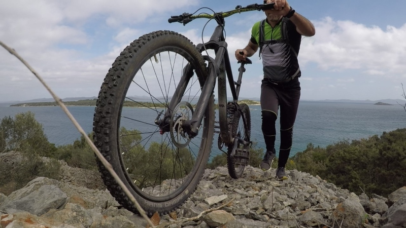 a man with a mountain bike on a hill