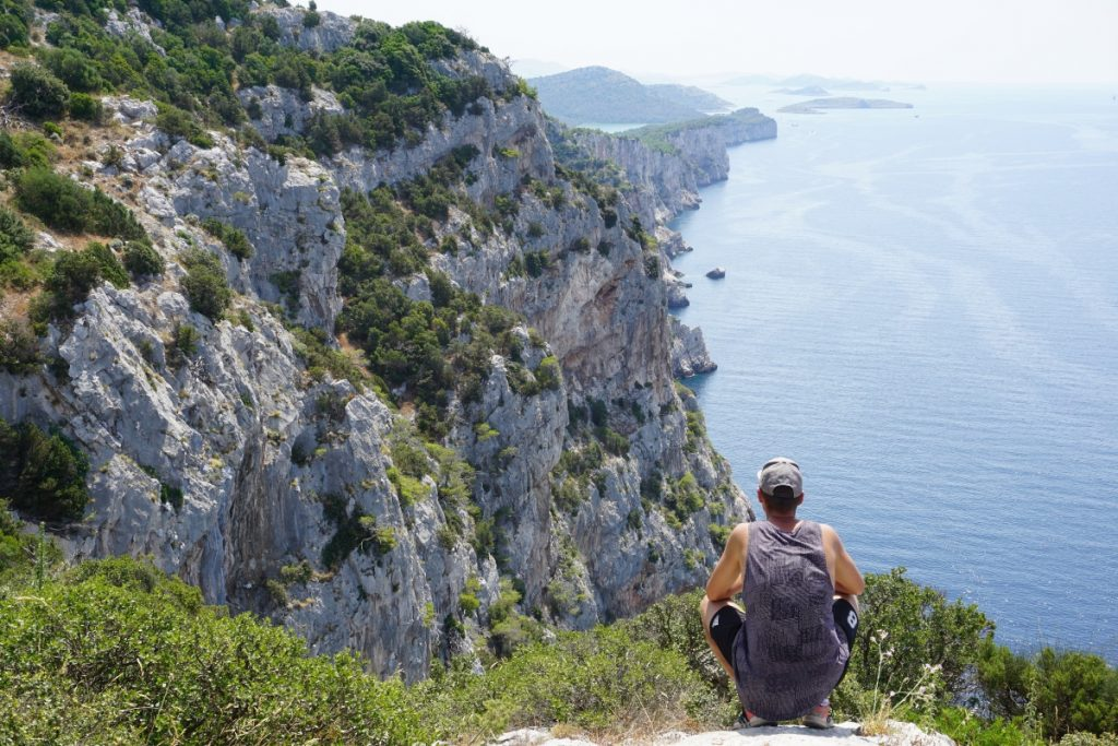 Mladić promatra stijene i more