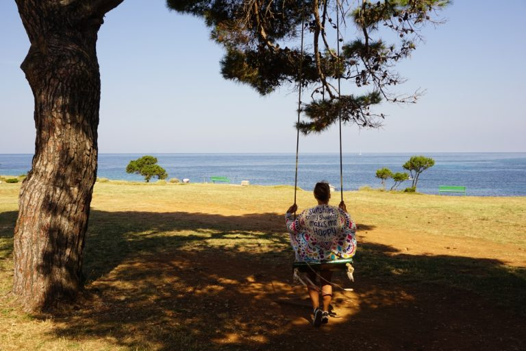 Djevojka na ljuljački ispod bora, pored plaže