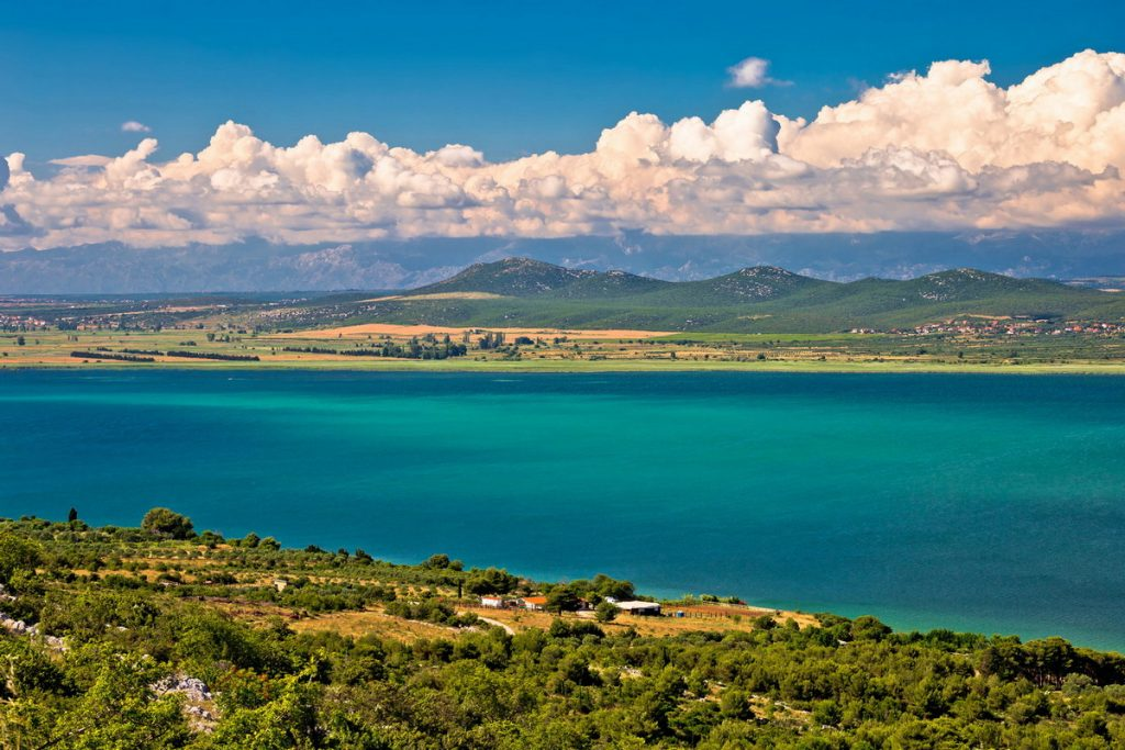 A view on Vrana lake near Zadar, Croatia with blue and green water and islands in the distance.