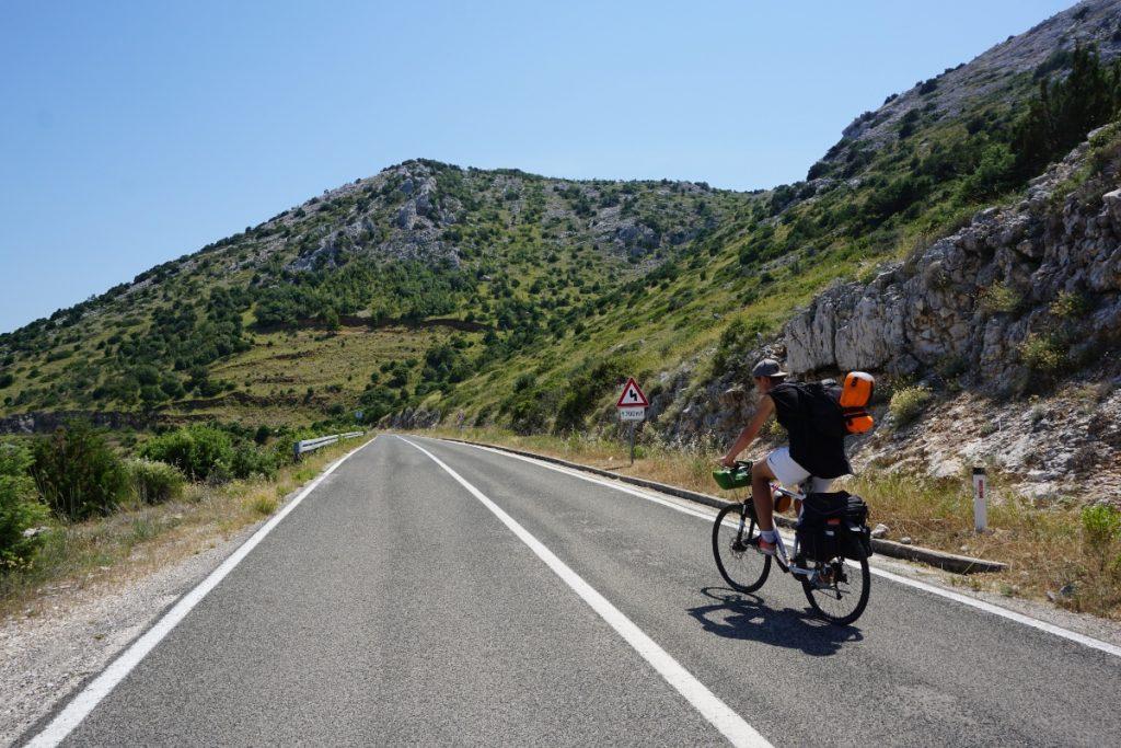a man cycling on an island road